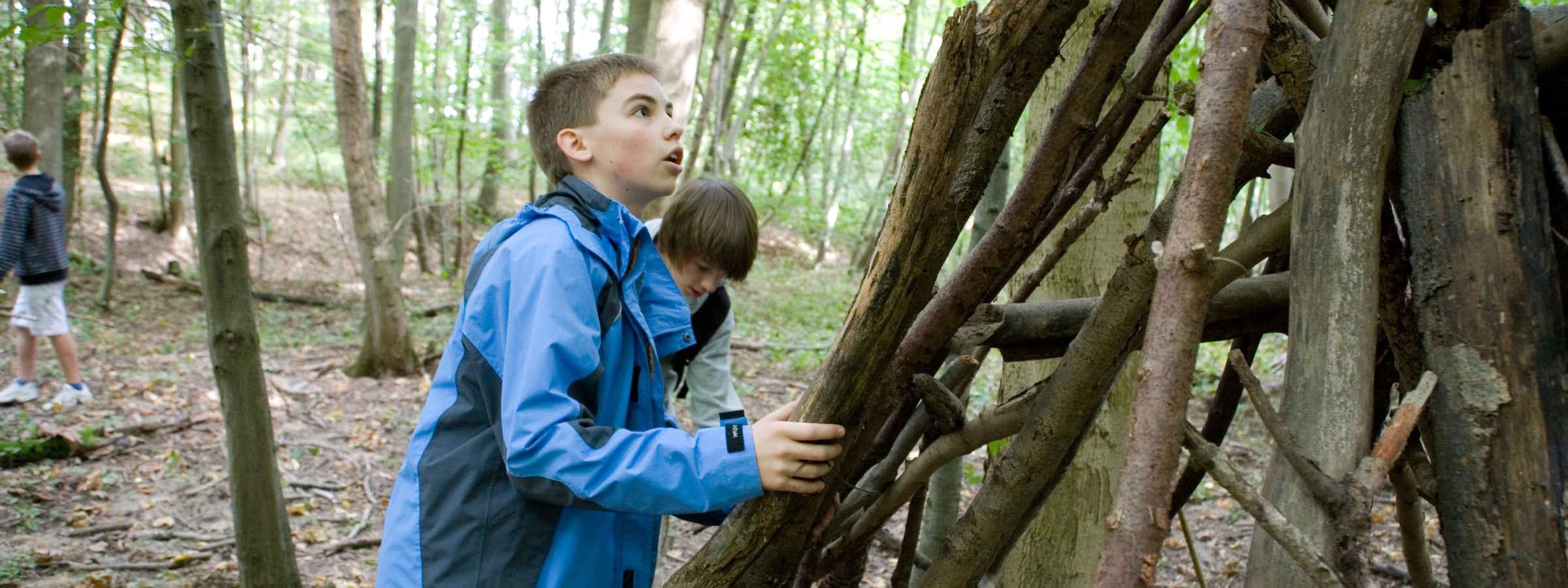 Zwei Jungen bauen eine Hütte im Wald